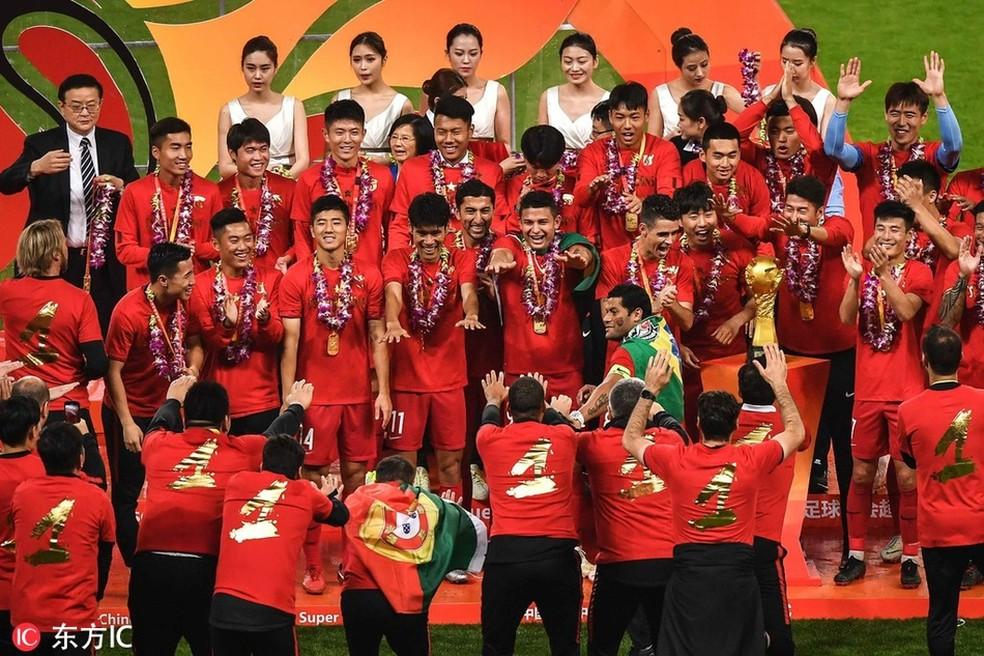 Elkeson estende as mãos, Oscar olha para o troféu, e Hulk se junta ao resto do time do Shanghai SIPG na comemoração do título chinês — Foto: Reprodução Sina.com