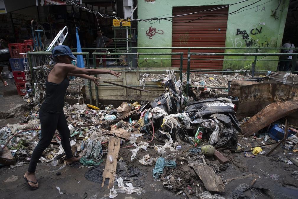 Mulher remove sujeira acumulada após tempestade em via da Rocinha, no Rio de Janeiro — Foto: Mauro Pimentel/AFP