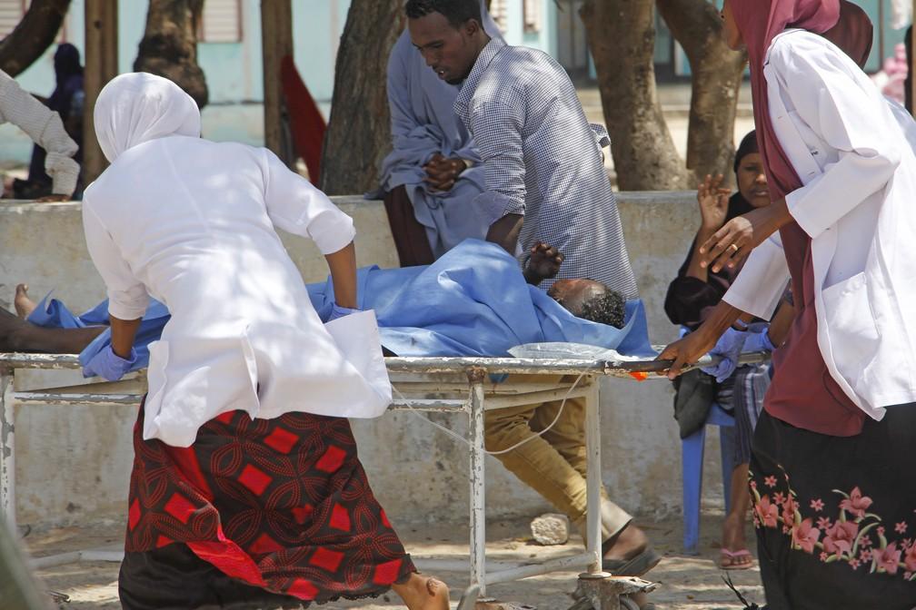 Trabalhadores médicos ajudam um homem ferido em um ataque com carro-bomba, no hospital Medina, em Mogadíscio, Somália, nesta segunda-feira (22). — Foto: Farah Abdi Warsameh/AP