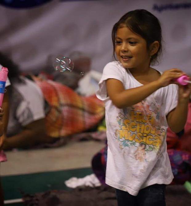 Menina hondurenha brinca de fazer bolhas de sabão (Foto: Héctor Alfaro)