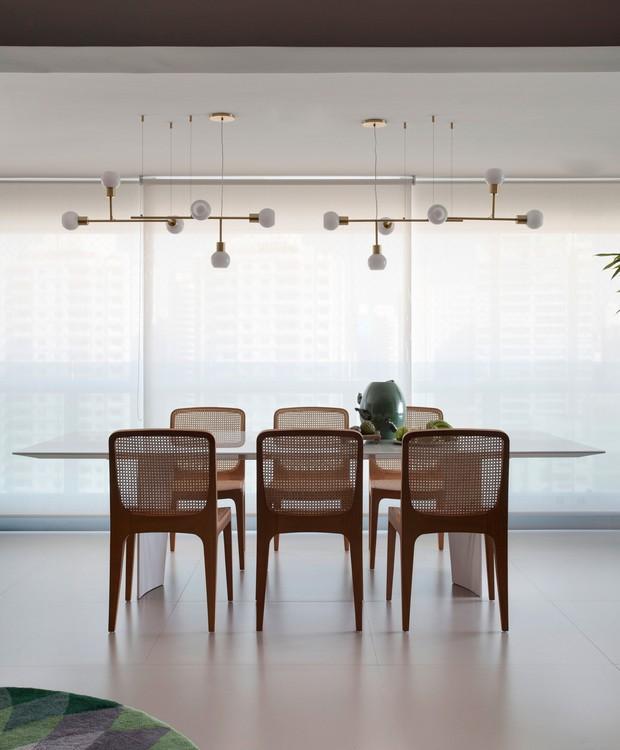 Ponto de encontro da família, a mesa de jantar na varanda (Breton) vem acompanhadas de cadeiras de Jader Almeida. No alto, pendentes douorados de Cristiana Bertolucci (Foto: Marco Antônio/Divulgação)