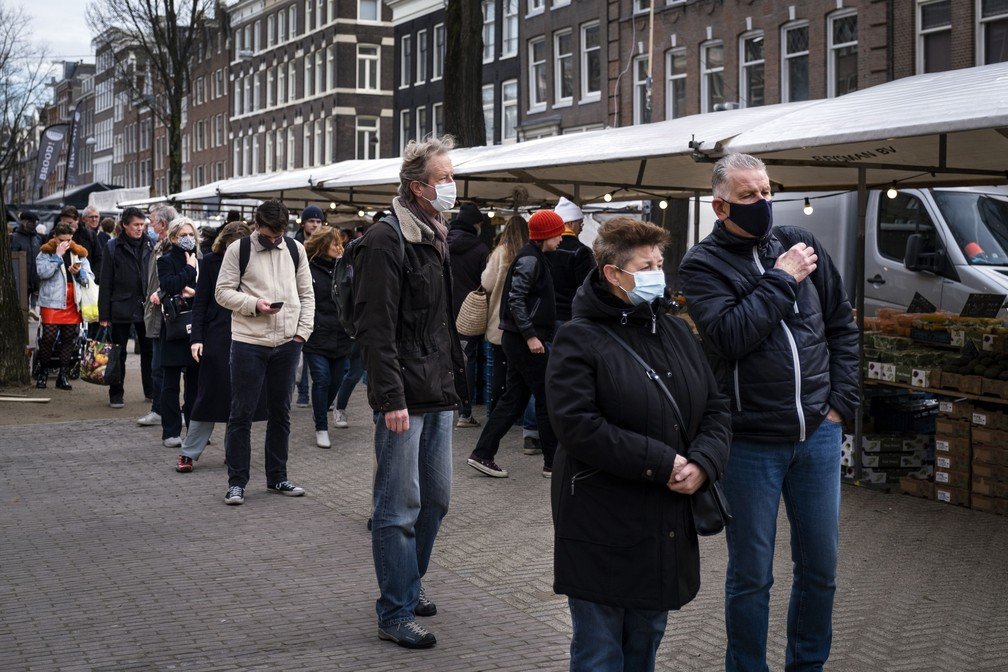 Pessoas de máscara contra a Covid-19 formam fila para fazer compras no mercado Lindengracht, em Amsterdã, em 19 de dezembro. — Foto: Ramon van Flymen/ANP/AFP
