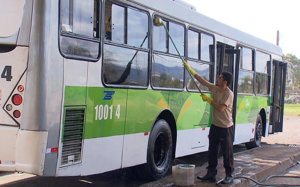 Funcionário da TCB lava ônibus com escovão e mangueira (Foto: TV Globo/Reprodução)