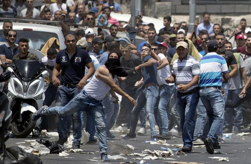 Manifestante palestino joga pedra contra as forças de segurança israelenses, nesta sexta-feira (21)  (Foto: Jack Guez / AFP )