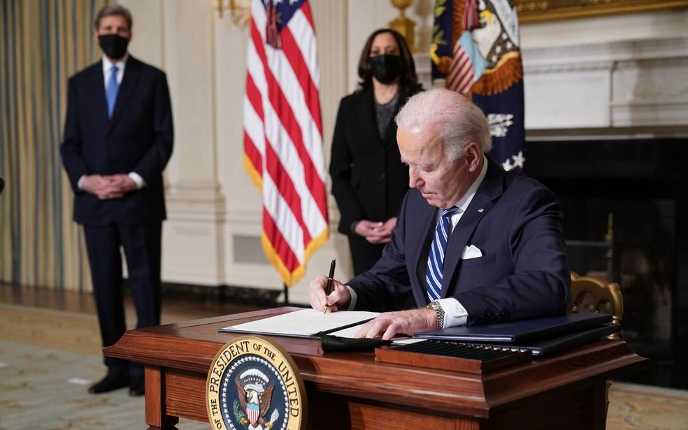 O presidente dos EUA, Joe Biden, assina atos executivos sobre meio ambiente, ao lado da vice-presidente, Kamala Harris, e do enviado especial presidencial para o Clima, John Kerry, na Casa Branca, na quarta-feira (27) — Foto: Mandel Ngan/AFP