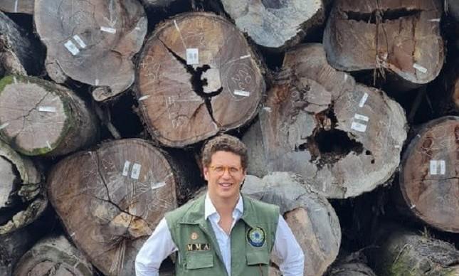 O ministro Ricardo Salles posa diante de madeira apreendida pelo Ibama