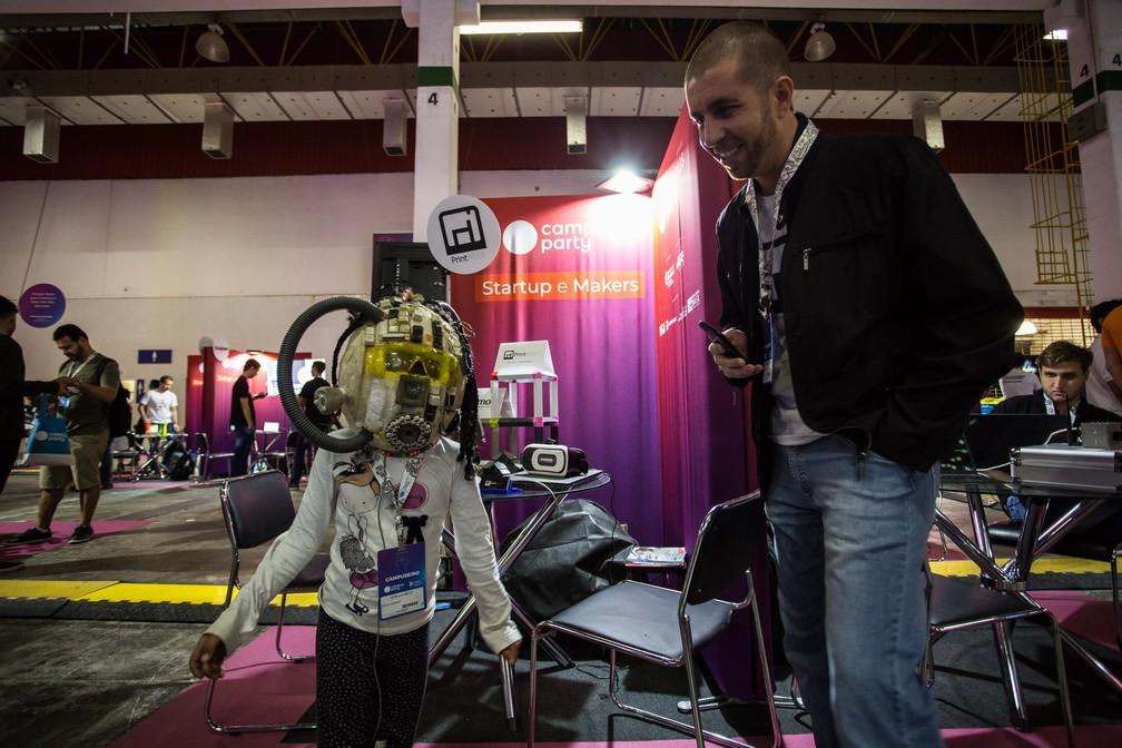 Menina brinca com uma máscara em área de start-ups e makers aberta ao público na Campus Party 2019 — Foto: Fábio Tito/G1