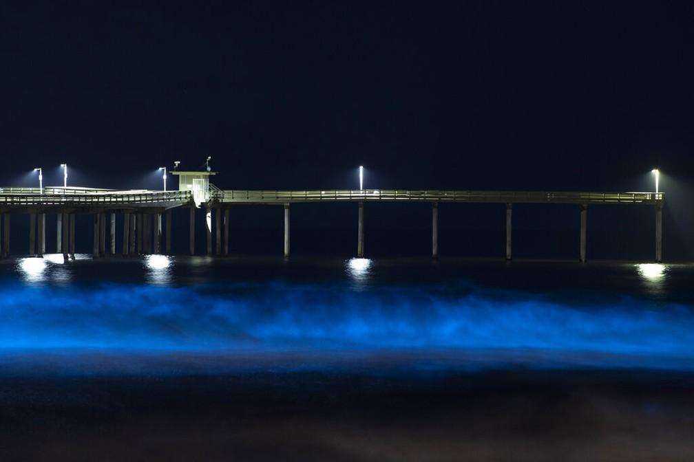 Ondas brilham com bioluminescência azul de algas nas águas do Oceano Pacífico em frente a um píer fechado na cidade de San Diego, na Califórnia, após medidas de isolamento por conta do novo coronavírus — Foto: Gregory Bull/AP