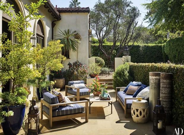 Jardins cercam a casa e poltronas estampadas criam áreas de descanso elegantes (Foto: Douglas Friedman/ Reprodução)