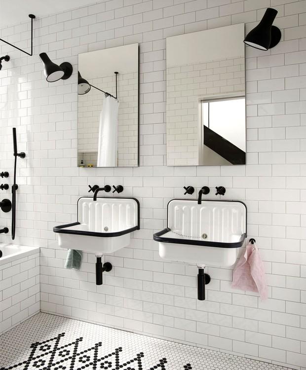 Nos banheiros, o branco dos azulejos é contrastado pelo preto dos acabamentos  (Foto: Indecora/ Reprodução)