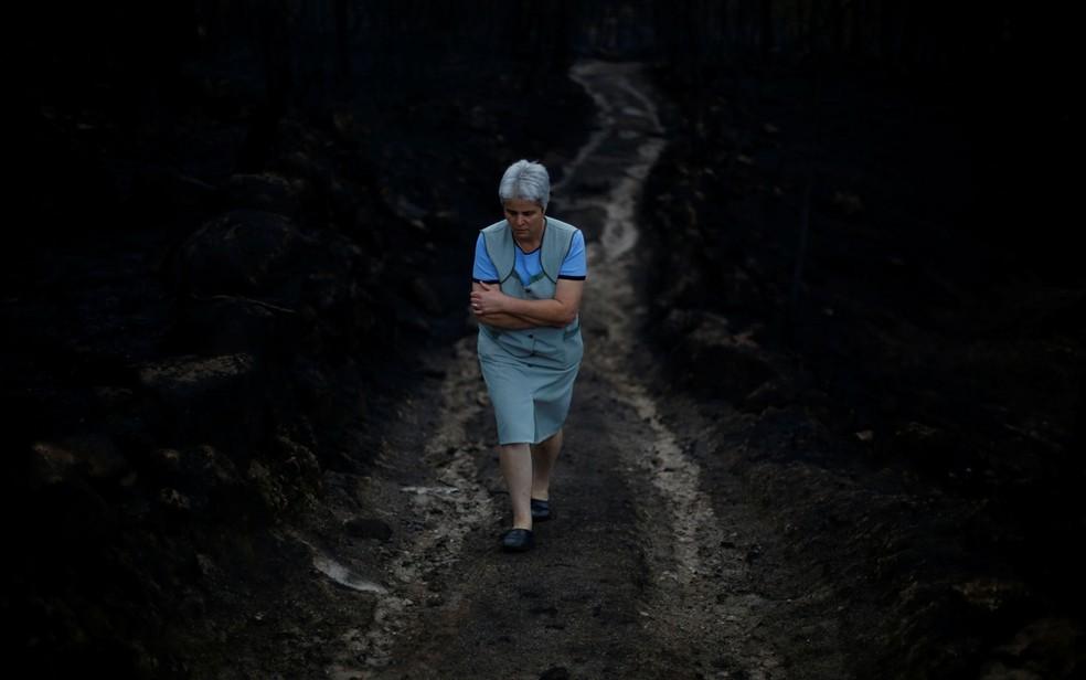 Mulher caminha por floresta queimada por incêndio em Vila Nova, perto de Vouzela, em Portugal, na terça-feira (17) (Foto: Reuters/Pedro Nunes)