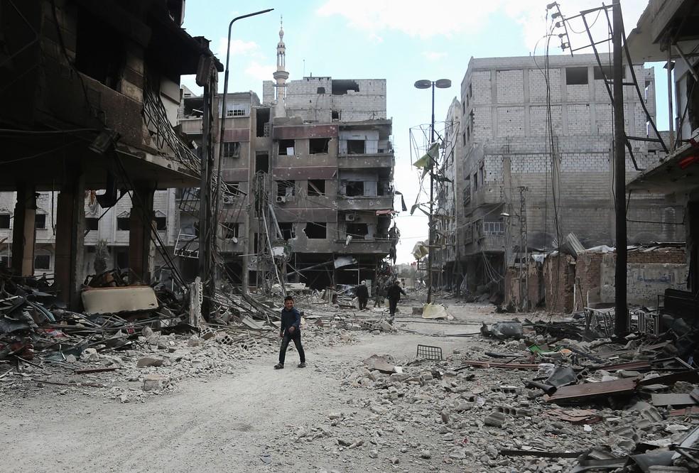 Sírios caminham nesta sexta-feira (16) em rua da cidade de Arbin, em Guta Oriental (Foto: Abdulmonam Eassa/AFP)
