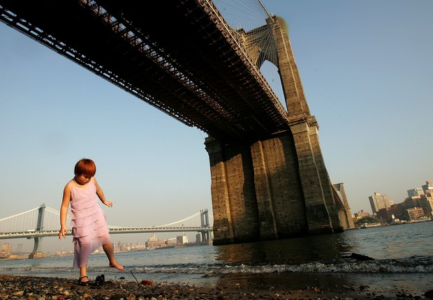 Nova York, Ponte do Brooklin NEW YORK - OCTOBER 05: Amy Chen, 8-years-old, tries to put her shoe back on while standing on the beach on the East River beneath the Brooklyn Bridge October 5, 2005 in New York City. New York is enjoying warm fall weather wit (Foto: Mario Tama/Getty Images)