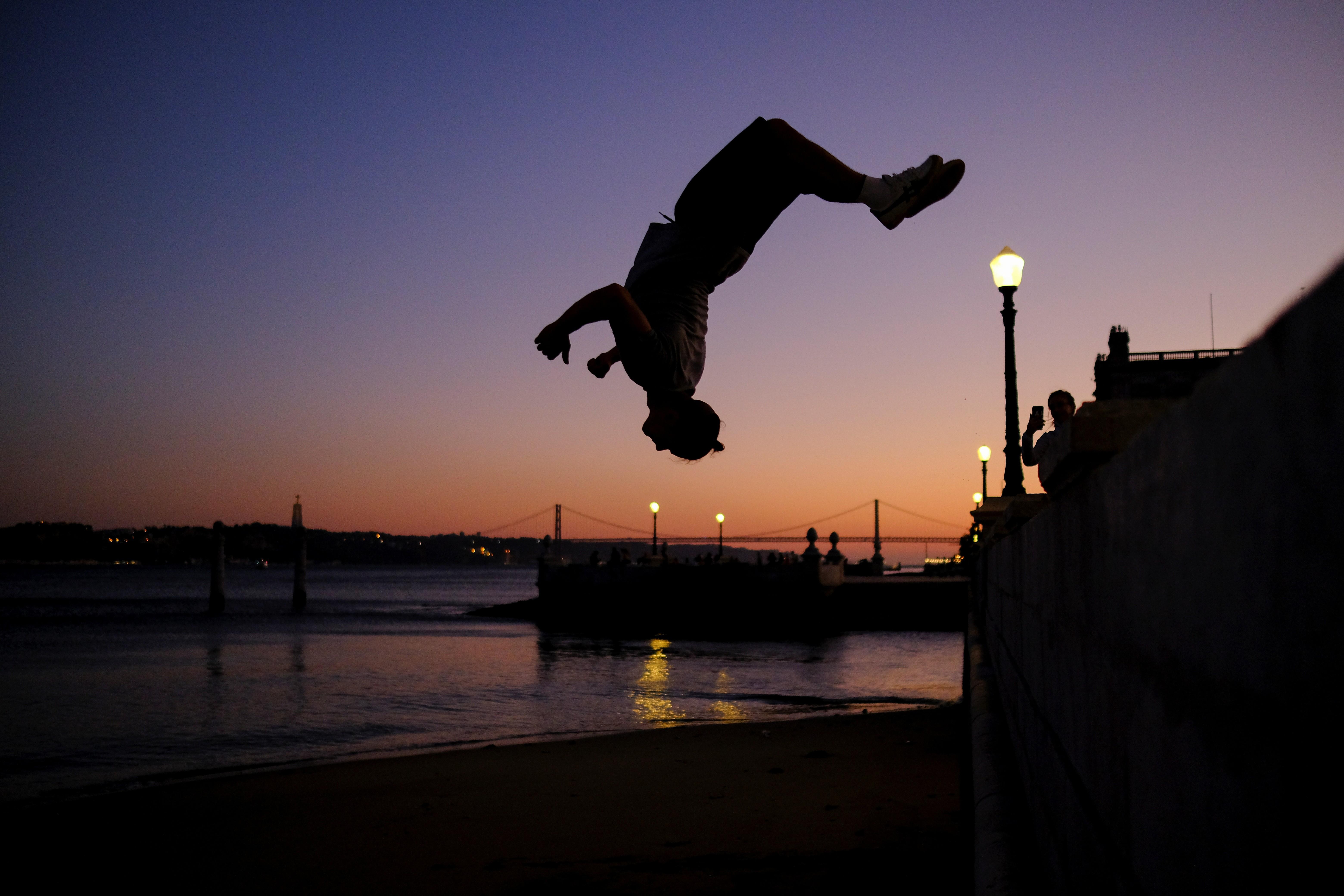 Homem salta em frente ao Rio Tejo, em Lisboa