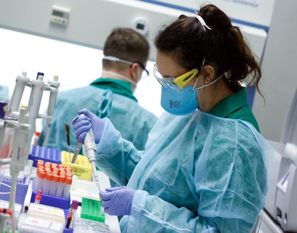 Funcionários em equipamento de proteção testam amostras para Covid-19 em um laboratório em Berlim, na Alemanha, nesta quinta-feira (26). — Foto: Axel Schmidt/Reuters