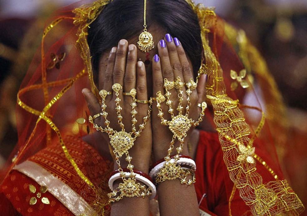 Noiva cobre o rosto enquanto aguarda sua vez em casamento coletivo na Índia  (Foto: Rupak De Chowdhuri/Reuters)