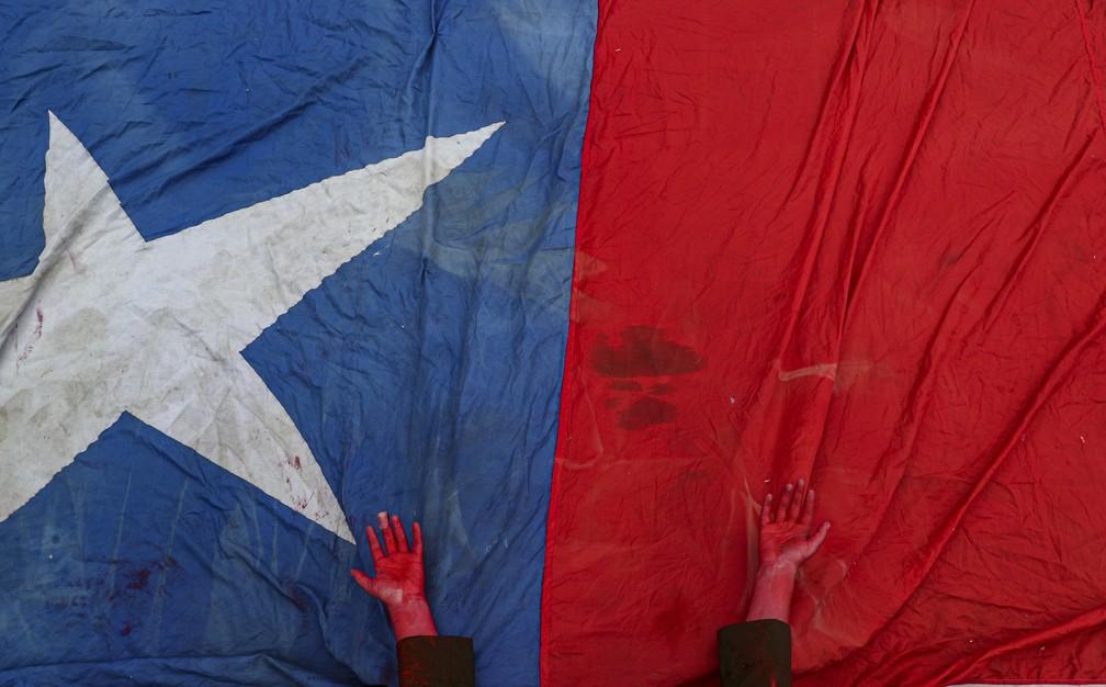 Manifestante com mão pintada de vermelho para simbolizar mortes nos protestos do Chile em bandeira durante protesto em Santiago neste domingo (27) — Foto: Esteban Felix/AP Photo