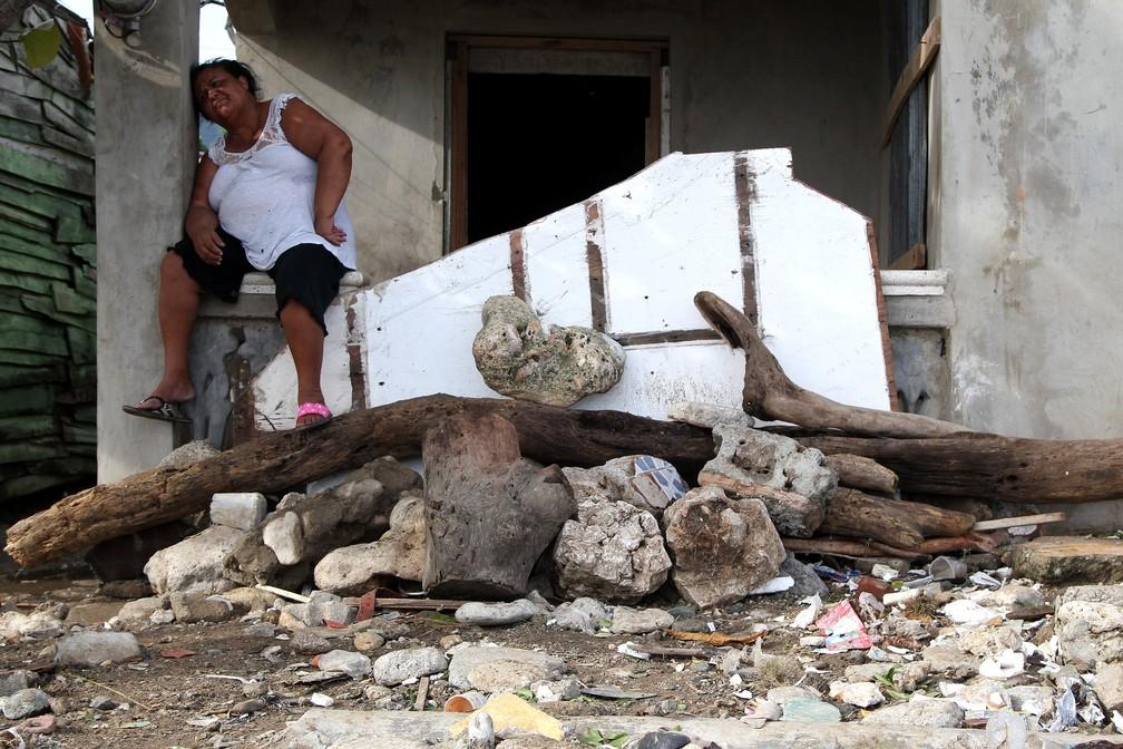 Mulher descansa antes de voltar a retirar os escombros de casa que caiu com a passagem do furacão Irma pelo Haiti. (Foto: Ricardo Rojas/Reuters)