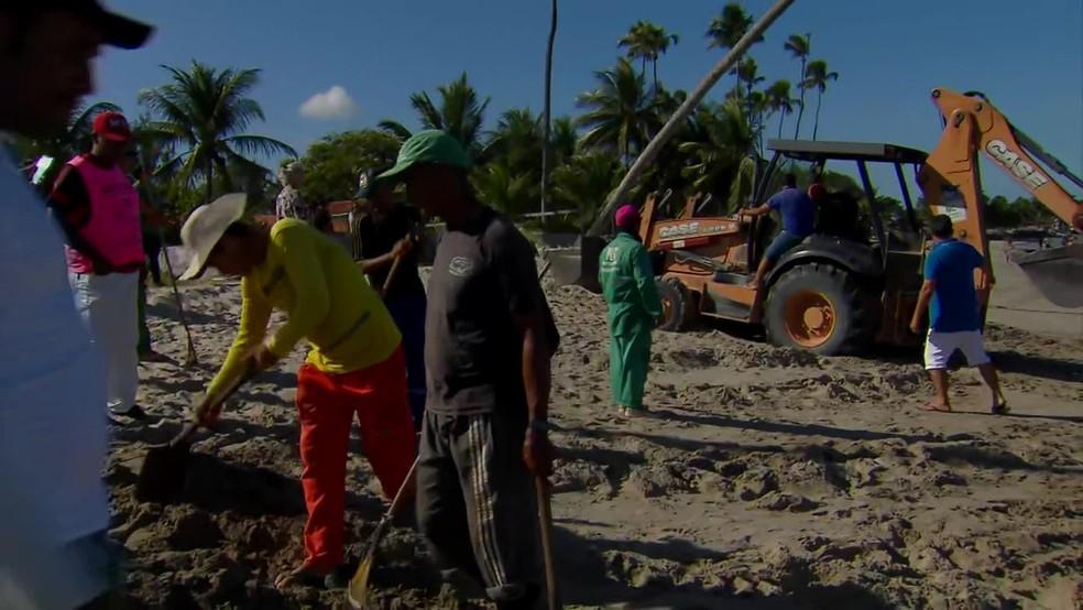 Moradores montaram mutirão para retirar manchas de óleo que apareceram na areia da praia, em São José da Coroa Grande, no Litoral Sul de Pernambuco — Foto: Reprodução/TV Globo