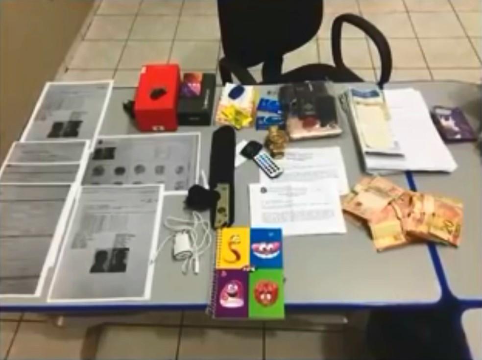 Com a dupla, a polícia encontrou documentos, cartões de crédito, celulares e dinheiro — Foto: Divulgação/Polícia Civil