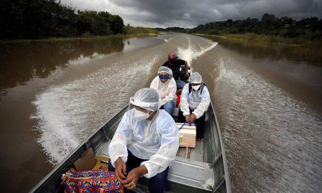 gentes municipais de saúde viajam de barco pelas margens do rio Solimões para aplicar a vacina AstraZeneca / Oxford contra o coronavírus na comunidade ribeirinha, em Manacapuru, Amazonas