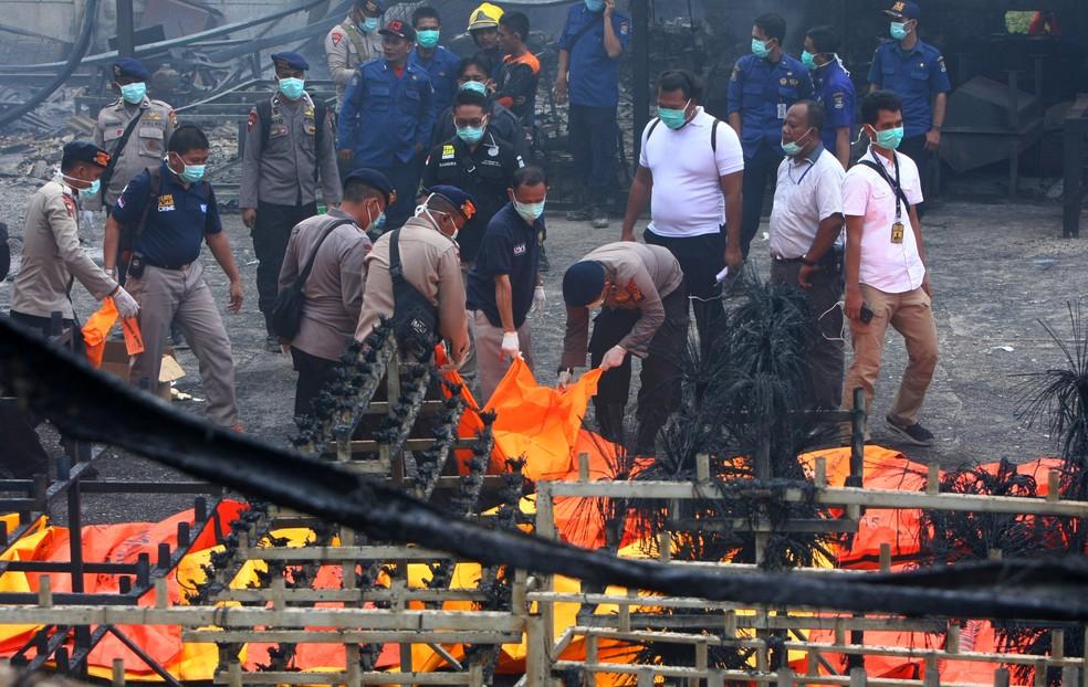 Policiais indonésios carregam corpos das vítimas de explosão de fábrica de fogos de artifício em Tangerang (Foto: Antara Foto/Muhammad Iqbal via Reuters)