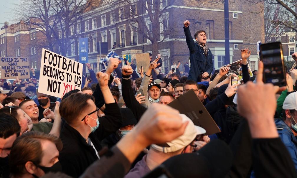 """Torcedores do Chelsea na porta do Stamford Bridge nesta terça-feira: """"O futebol pertence a nós, não a vocês"""", diz placa — Foto: AFP"""