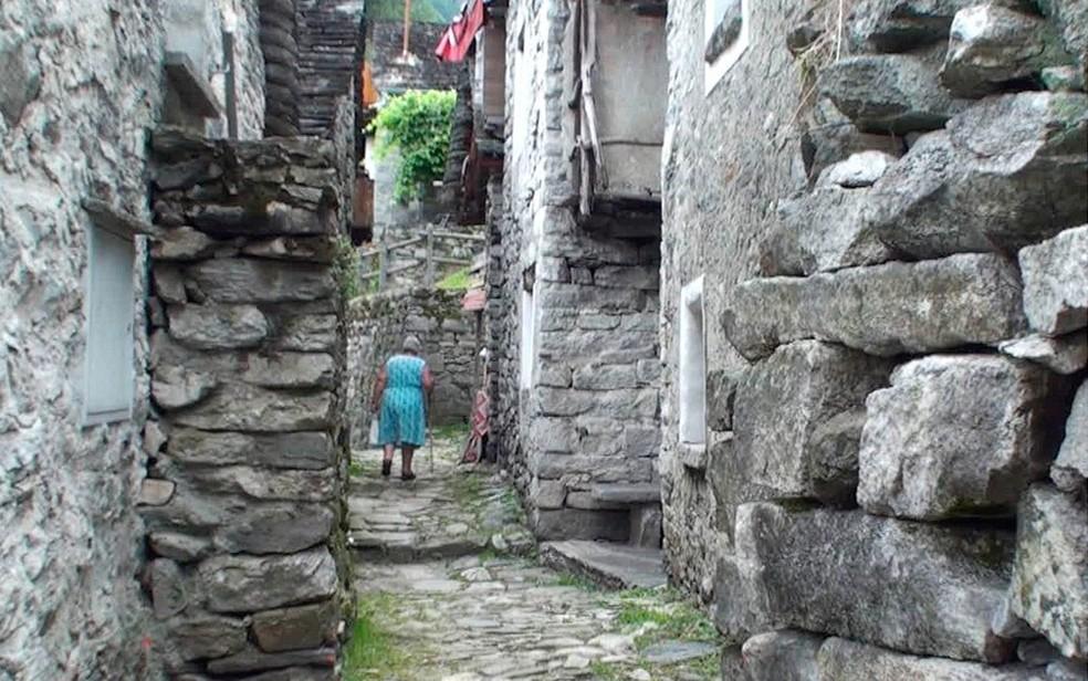 Senhora caminha por uma rua estreita de Corippo, ladeada por construções de pedra (Foto: BBC)