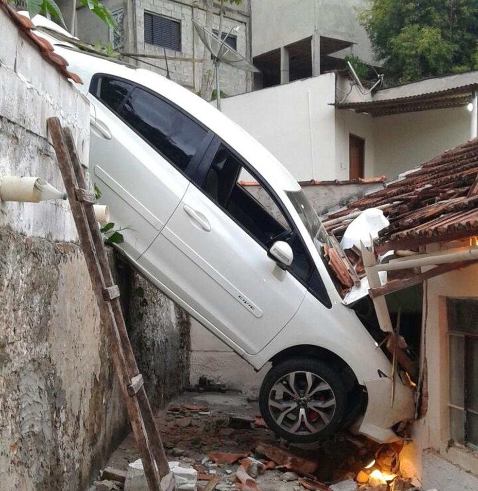 Carro caiu em cima do telhado de casa em Brazópolis (MG) (Foto: Cristiane Carneiro)