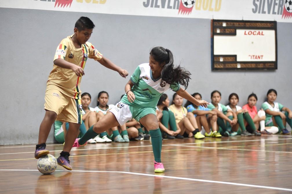 Menina e menino disputam bola em escolinha para bolivianos em São Paulo — Foto: Marcos Ribolli