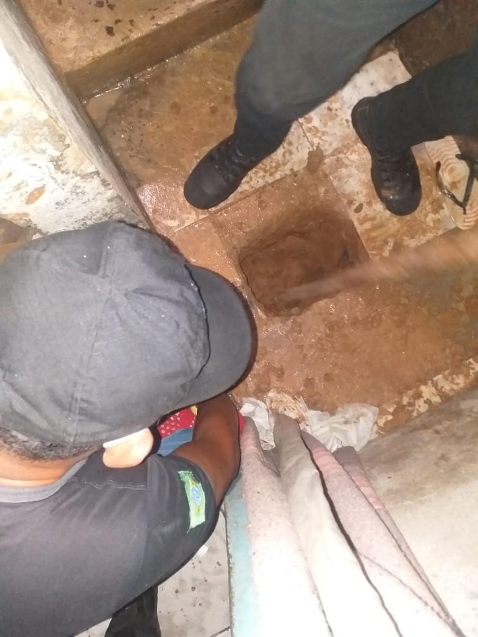 Agentes medem profundidade de buraco feito por presos em cela — Foto: Polícia Penal/Divulgação
