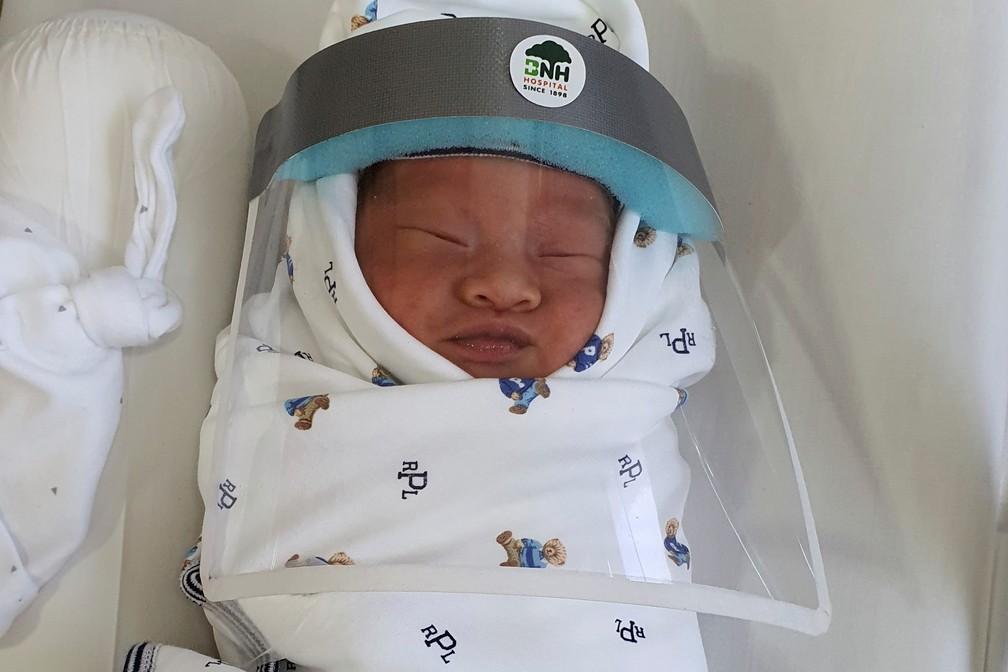 2 de abril - Bebê recém-nascido é visto em um hospital usando protetor facial, em Bangcoc, na Tailândia, durante a epidemia do novo coronavírus (COVID-19) — Foto: Handout via Reuters