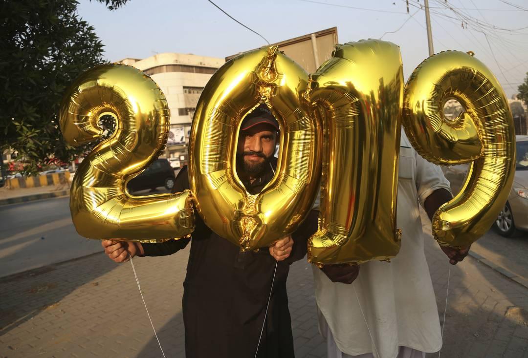 Vendedor segura balões na véspera do Ano Novo, em Karachi, no Paquistão