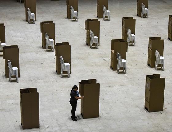Uma trabalhadora prepara cabines de votação antes do primeiro turno das eleições colombianas. Foram às urnas 53% dos eleitores, proporção acima da média das últimas quatro décadas (Foto: LUIS ROBAYO/AFP)