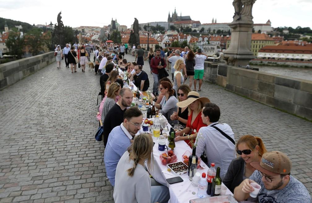 Moradores jantam ao redor de uma mesa de 500 metros na ponte medieval Charles Bridge em Praga, na República Tcheca, nesta terça (30) — Foto: David W Cerny/Reuters