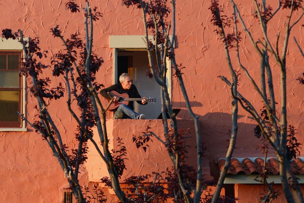 Danny Wertheimer toca violão e canta para os vizinhos de sua varanda em Oakland, na Califórnia, em 21 de março, dois dias após o governador da Califórnia implementar uma 'ordem de permanência em casa' em todo o estado — Foto:  Kate Munsch/Reuters