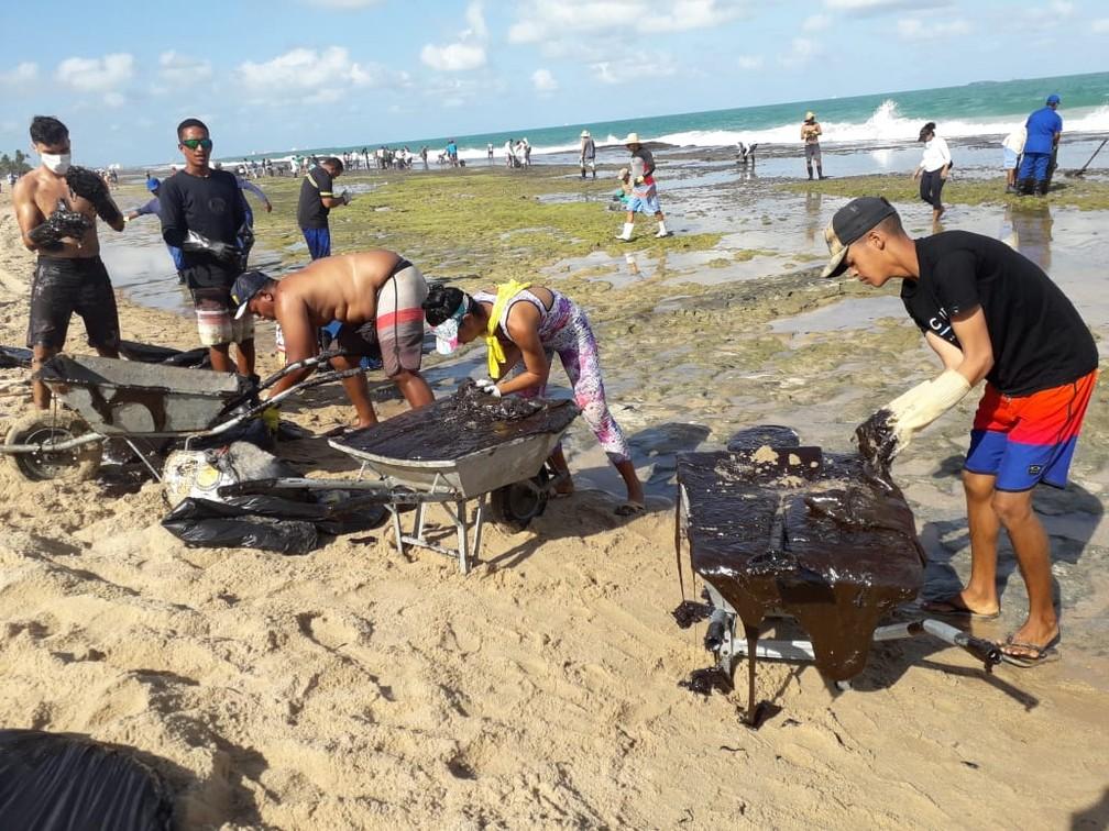 Voluntários retiram óleo de arrecife na praia de Muro Alto, em Ipojuca — Foto: Luna Markman