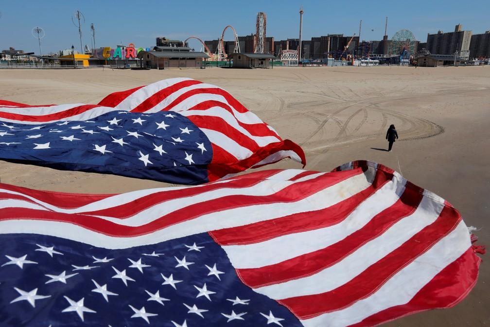 Bandeiras dos EUA em praia de Coney Island, em Nova York, neste domingo (19) — Foto: Andrew Kelly/Reuters