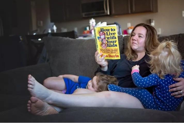 Mãe lê livro de dicas para criação com duas crianças no colo (Foto: Reprodução/Pictures By GG)