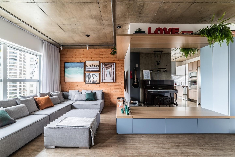 Ambiente com piso vinílico, sofá cinza com mini estúdio de musica.