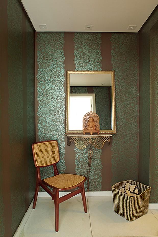 No hall de entrada, o aparador francês de ferro foi descoberto na casa da avó da moradora. Ao lado, cesto com chinelinhos, como manda o figurino oriental. Projeto da arquiteta Gabriela Marques (Foto: Victor Affaro)