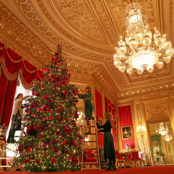 Royal Collection Trust members of staff put the finishing touches to a 15ft Christmas tree in the Crimson Drawing Room at Windsor Castle, Berkshire. (Photo by Steve Parsons/PA Images via Getty Images) (Foto: PA Images via Getty Images)