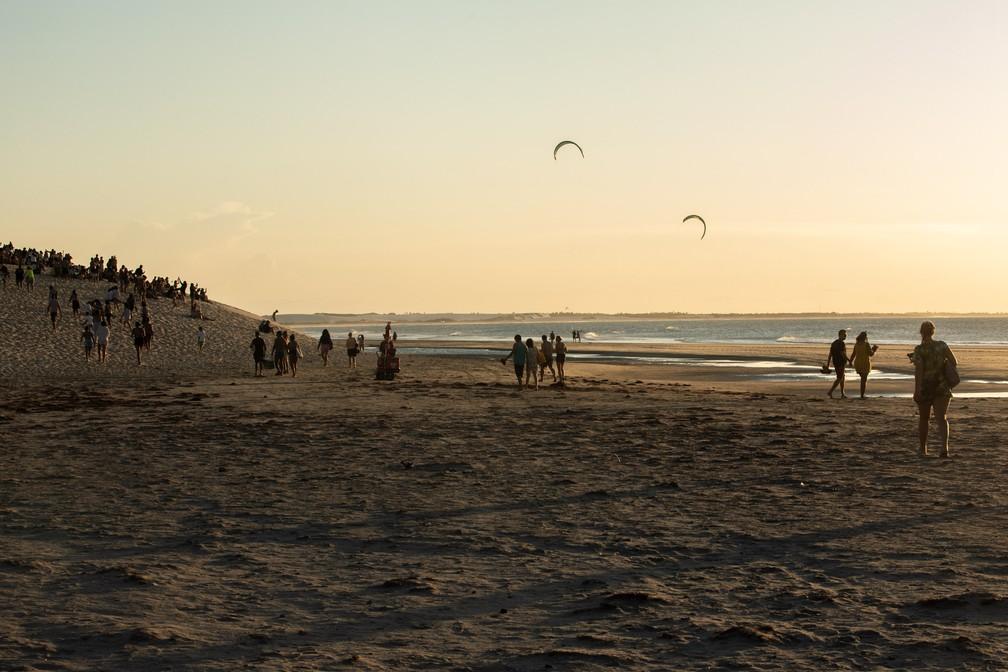 Com a aproximação do pôr do sol, turistas caminham até a duna da praia central — Foto: Celso Tavares/G1