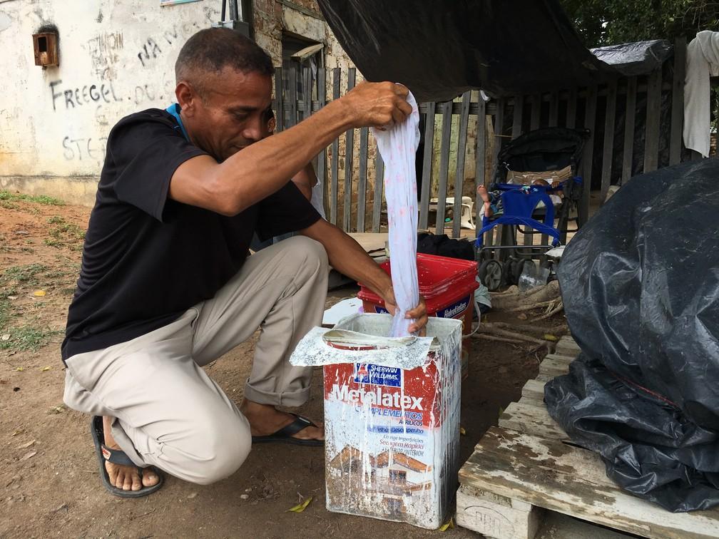 Há um mes vivendo na rua, Luiz Rosalez, 49, lava roupas enquanto cuida do filho de 1 mês (Foto: Emily Costa/G1 RR)
