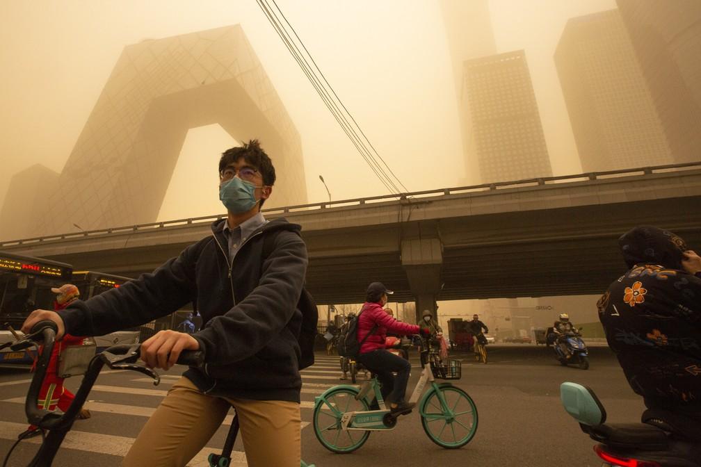 Ciclistas em meio a tempestade de areia durante o horário de rush no distrito comercial de Pequim nesta segunda-feira (15) — Foto: Mark Schiefelbein/AP