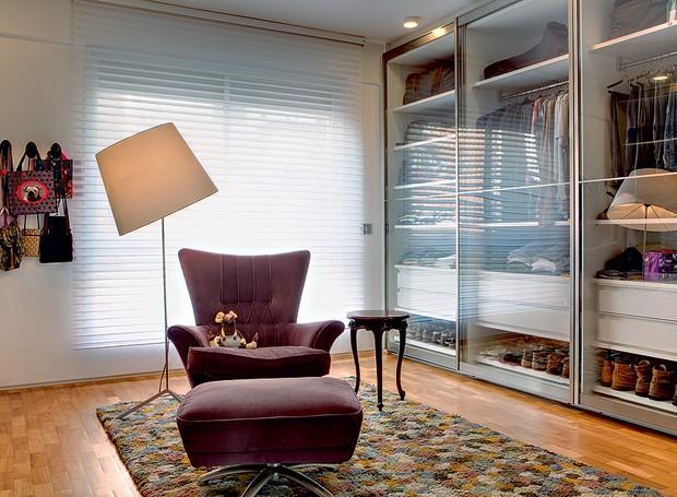 A área de vestir tem armários com portas de vidro deslizantes. Sobre o tapete da espanhola Nanimarquina, a poltrona e a mesinha dão o suporte ideal. Reforma da SAO Arquitetura (Foto: Edu Castello)