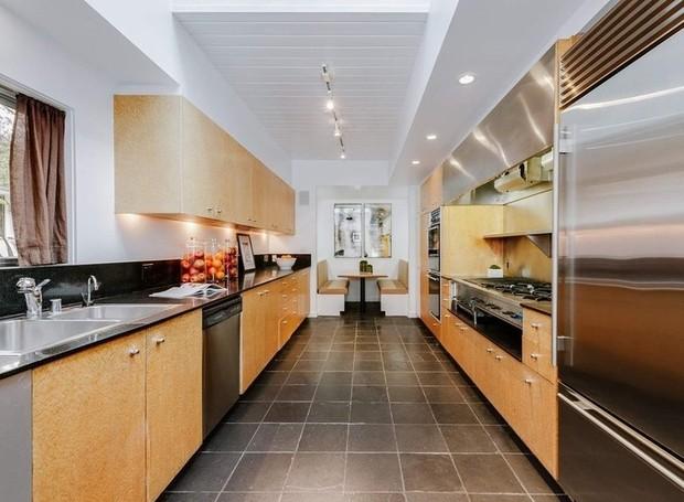 A cozinha é feita de inox e madeira (Foto: Homes.com)