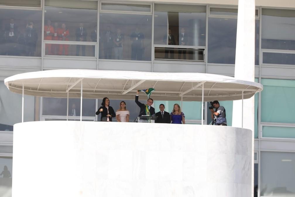 O novo presidente do Brasil, Jair Bolsonaro, acena para apoiadores ao lado de sua esposa, Michelle Bolsonaro, após receber a faixa presidencial do ex-presidente Michel Temer, no Palácio do Planalto, em Brasília   — Foto: Fábio Tito/G1