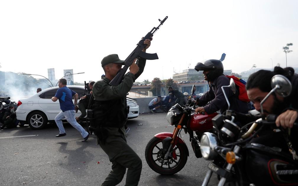 """Soldados e pessoas reagem ao som de disparos perto da base aérea conhecida como """"La Carlota"""" em Caracas — Foto: Carlos Garcia Rawlins/Reuters"""