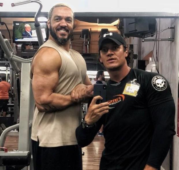 Belo mostrando os músculos ao lado do seu personal (Foto: Reprodução/Instagram)